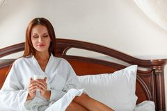 Smiling woman in bedroom drinking coffee on bed Stock Images