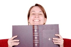 Smiling woman behind book. Young woman hiding behind the book, smiling at you Royalty Free Stock Images