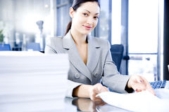 Smiling woman behind a desk full of paperwork Stock Photography