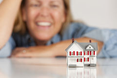 Smiling Woman Behind Model House on White Table Royalty Free Stock Photos