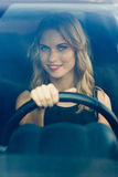 Smiling woman behind the wheel of car, vertical composition. Smiling woman behind the wheel of car, shot through windshield. Vertical composition Stock Photography