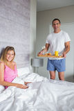 Smiling woman being brought breakfast in bed by husband. Smiling women being brought breakfast in bed by husband looking at camera at home in bedroom Stock Photo