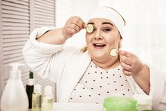 Smiling woman being contented with hand-made beauty hacks. Woman putting cucumbers. Smiling woman being contented with hand-made beauty hacks while covering her royalty free stock photo