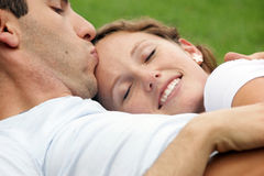 Smiling woman being kissed on forehead by husband. Smiling woman with eyes closed resting her head on her husband's chest as he kisses her forehead Royalty Free Stock Images