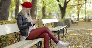 Smiling woman in beret using smartphone stock footage