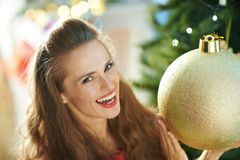 Smiling woman with big gold Christmas ball near Christmas tree stock photos