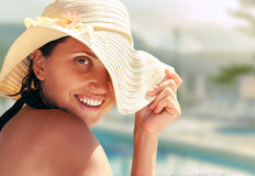 Smiling woman in big summer hat near the pool Stock Photo
