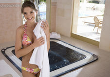 Smiling woman in bikini standing in front of hot tub Royalty Free Stock Photography