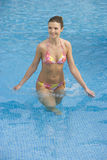 Smiling woman in bikini standing in swimming pool Royalty Free Stock Images