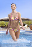Smiling woman in bikini walking in swimming pool Stock Image