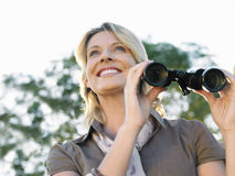 Smiling Woman With Binoculars Outdoors Stock Photo
