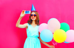 Smiling woman in a birthday cap is taking a picture on a smartphone with an air colorful balloons over pink background Stock Photography