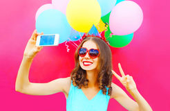 Smiling woman in a birthday cap is taking a picture on a smartphone with an air colorful balloons on pink background Royalty Free Stock Photo