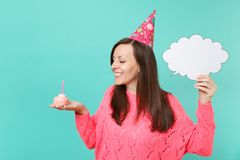 Smiling woman in birthday hat looking on cake with candle, hold empty blank Say cloud, speech bubble for promotional. Content isolated on blue background stock images