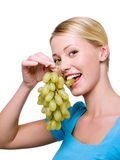 Smiling woman bits the grape Royalty Free Stock Photography