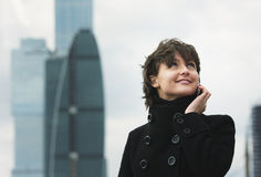 Smiling woman in black on cellphone stock photo