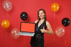 Smiling woman in black dress showing thumb up, holding laptop pc computer with blank black empty screen on bright red. Background air balloons. Happy New Year stock image