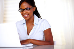 Smiling woman with black glasses working on laptop Stock Photos