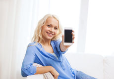 Smiling woman with blank smartphone screen at home Royalty Free Stock Photos