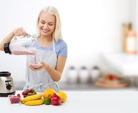 Smiling woman with blender and fruit milk shake. Healthy eating, cooking, vegetarian food, dieting and people concept - smiling young woman with blender and Stock Images
