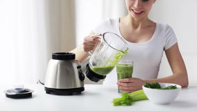 Smiling woman with blender jar and green shake stock video