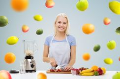 Smiling woman with blender preparing fruit shake. Healthy eating, cooking, vegetarian food, dieting and people concept - smiling young woman with blender Stock Images