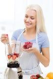 Smiling woman with blender preparing shake at home Stock Photo