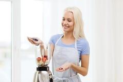 Smiling woman with blender preparing shake at home Stock Image