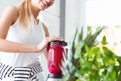 Smiling woman blending red smoothie. Close-up of smiling vegan woman in casual outfit blending red smoothie in kitchen mixer stock image