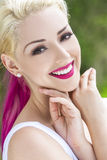 Smiling Woman With Blond and Magenta Pink Hair. Outdoor portrait of a beautiful smiling woman or girl with brown eyes, perfect teeth, blond and magenta pink hair Stock Images