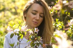 Smiling woman in blossoming bush in the sunny summer day stock photo