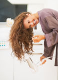 Smiling woman blow drying hair in bathroom Royalty Free Stock Photography