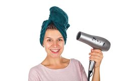 Smiling woman blow drying her hair. Smiling young woman holding a blow dryer after bath on isolated background Stock Photos