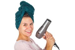 Smiling woman blow drying her hair. Smiling young woman holding a blow dryer after bath on isolated background Royalty Free Stock Photography