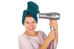 Smiling woman blow drying her hair. Smiling young woman holding a blow dryer after bath on isolated background Royalty Free Stock Photo