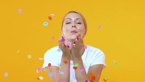 Smiling woman blowing confetti against yellow background, party entertainment. Stock footage stock video