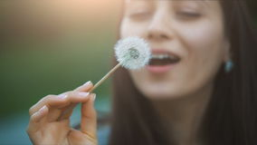 Smiling Woman Blowing on a Dandelion. Woman blowing dandelion seeds at sunset stock footage