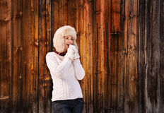 Smiling woman blowing warm breath on her hands near wood wall Stock Photos