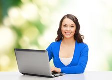 Smiling woman in blue clothes with laptop computer Royalty Free Stock Image