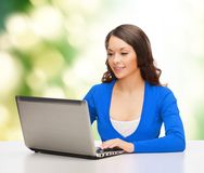 Smiling woman in blue clothes with laptop computer Royalty Free Stock Images