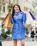 Smiling woman in blue coat with purchases Royalty Free Stock Photos