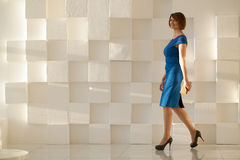 Smiling woman in blue dress walking against modern wall with wallet in hand Stock Images
