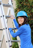 Smiling woman in blue helmet climbing on aluminum ladder Royalty Free Stock Photos