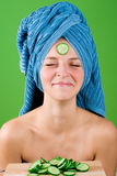 Smiling woman in blue towel and mask from cucumber Stock Image