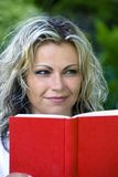 Smiling woman with book. Smiling young woman with red book Royalty Free Stock Photo