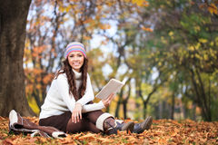 Smiling woman with book in autumn park royalty free stock photos