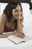 Smiling Woman With Book In Bed Stock Photos
