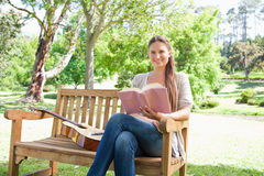 Smiling woman with a book and a guitar sitting on a bench Stock Photography