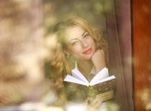 Smiling woman with book at home, view through window glass Stock Photography