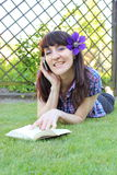 Smiling woman with book and mobile phone in sunny garden Royalty Free Stock Images